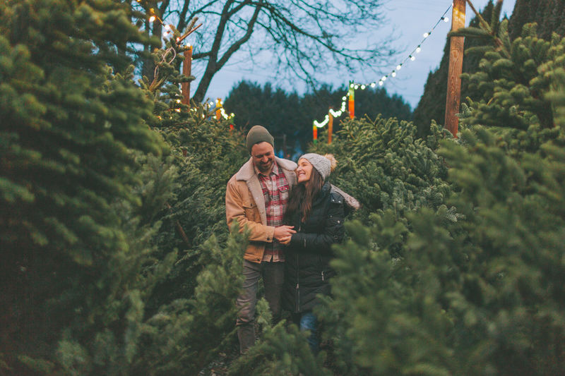 Couple amidst plants during sunset
