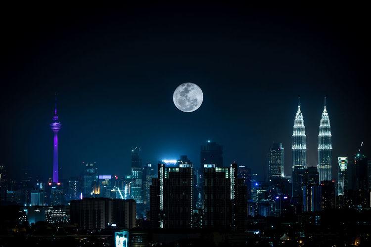 Full moon over illuminated modern cityscape at night