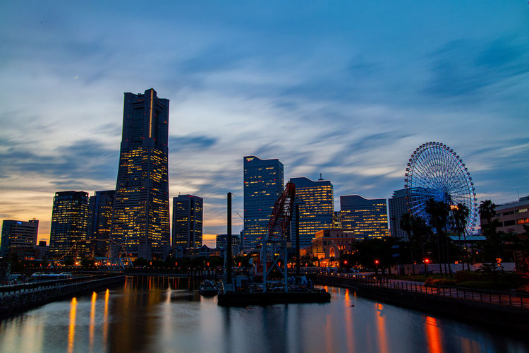 Illuminated buildings by river against sky in yokohama city