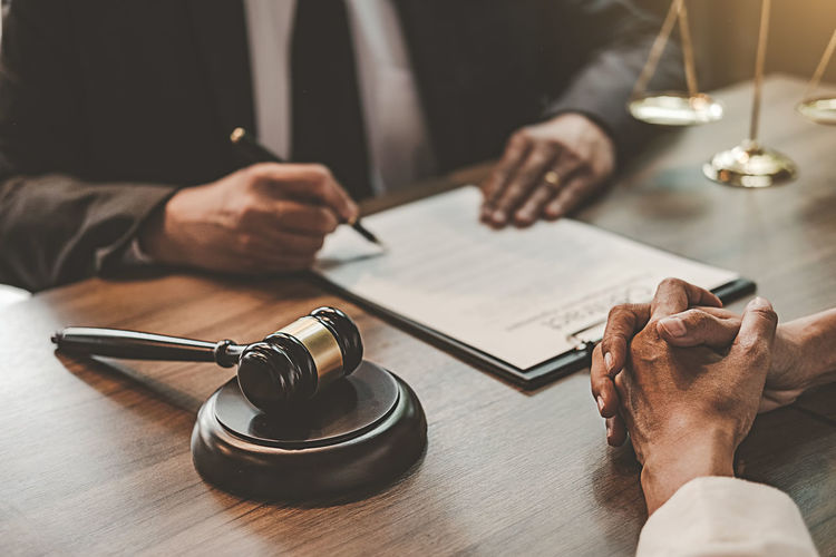 Judge signing contract while client sitting with hands clasped at table in office