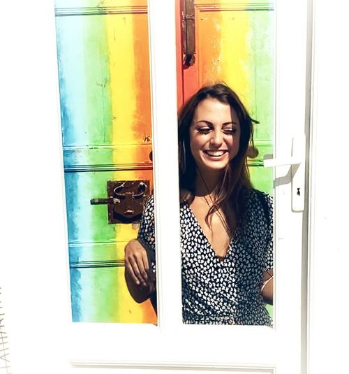 Portrait of smiling young woman in glass window