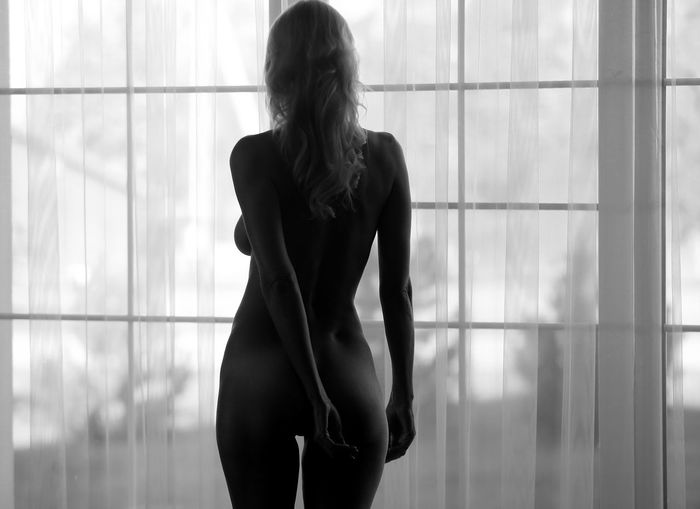 Rear view of naked woman standing by window at home