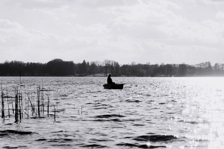 Silhouette Man Boating On Lake Against Cloudy Sky