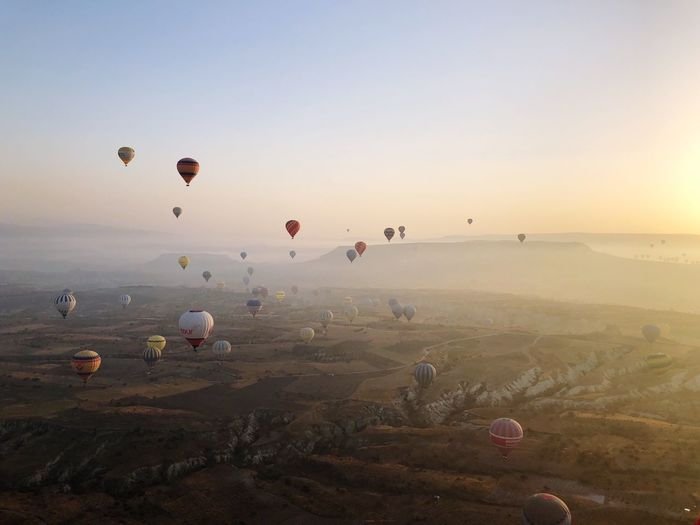 Hot air balloons flying over landscape at cappadocia during sunset