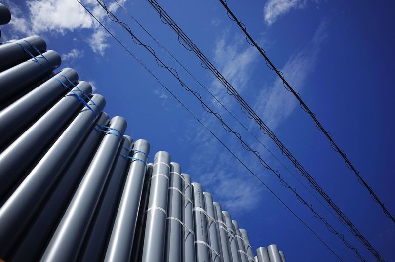 Low angle view of pipes and power lines against blue sky