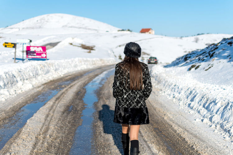 Rear View One Person Snow Real People Nature Day Winter Transportation Lifestyles Water Leisure Activity Clothing Cold Temperature Walking Road Full Length Women Outdoors Warm Clothing Hairstyle