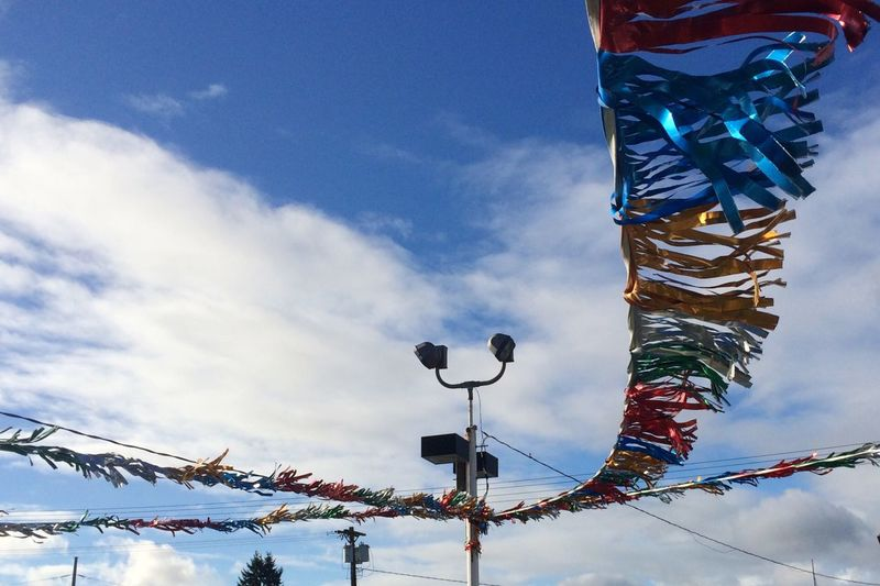 Low angle view of bunting against cloudy sky