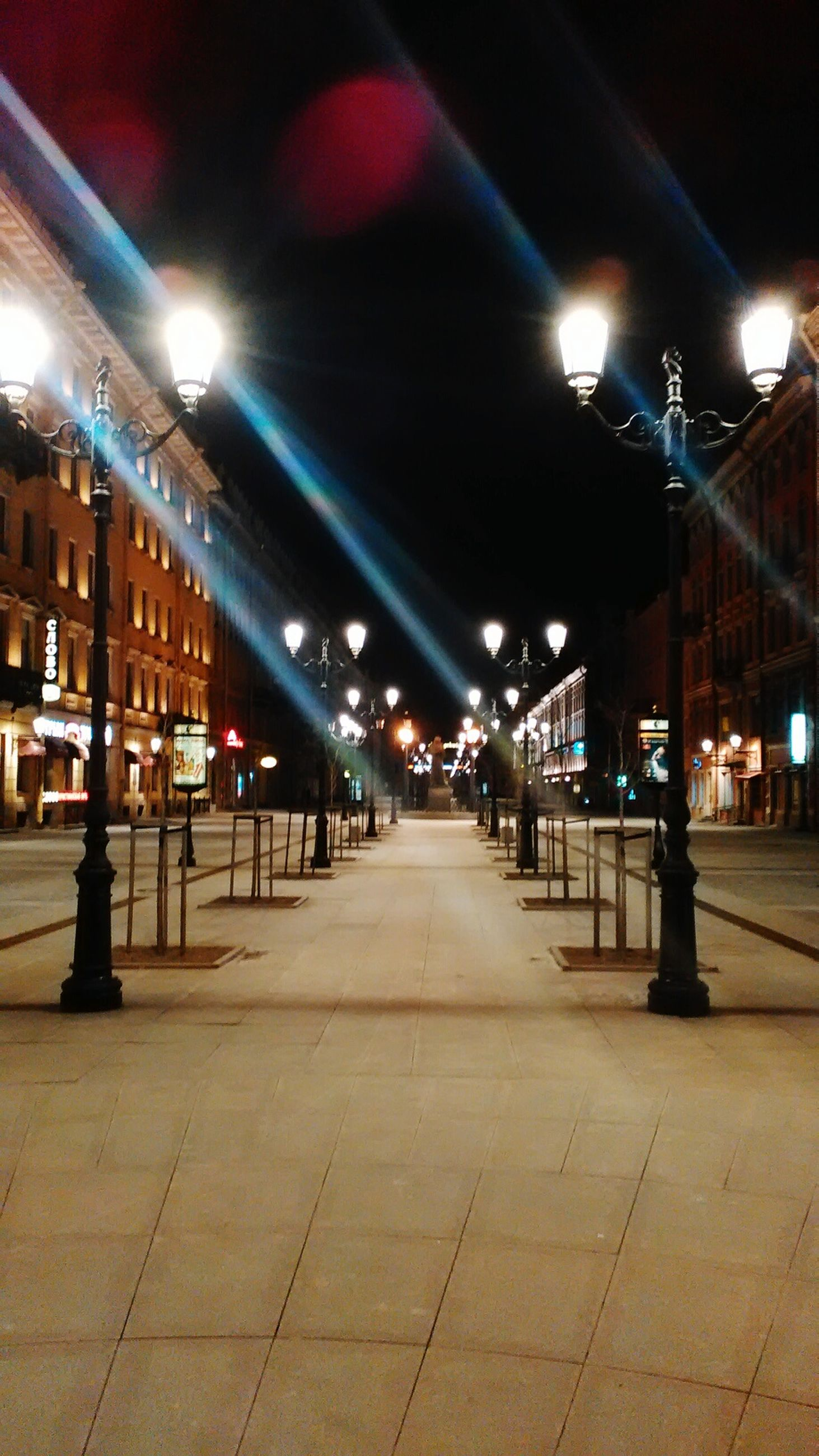 illuminated, night, built structure, architecture, lighting equipment, the way forward, street light, city, building exterior, transportation, diminishing perspective, incidental people, city life, empty, street, vanishing point, light - natural phenomenon, electric light, in a row, outdoors
