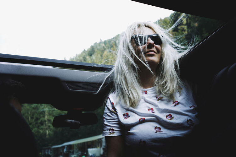 Low angle view of woman wearing sunglasses in car at sun roof