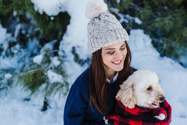 Portrait of woman with dog in snow