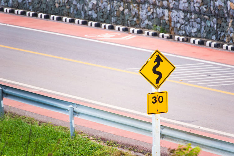 Traffic signs on a seaside road.Thailand Arrow Symbol Communication Day Direction Directional Sign Focus On Foreground Guidance Marking Nature No People Number Outdoors Road Road Marking Road Sign Sign Symbol Text Transportation Yellow