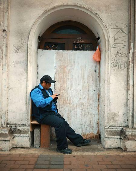 Textual Full Length Men Sitting Wireless Technology Doorway Door Holding Architecture Entryway Arch Entrance Front Door Closed Door Closed The Portraitist - 2018 EyeEm Awards The Street Photographer - 2018 EyeEm Awards