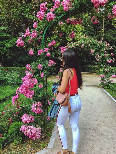 Full length of woman standing by pink flowers in park