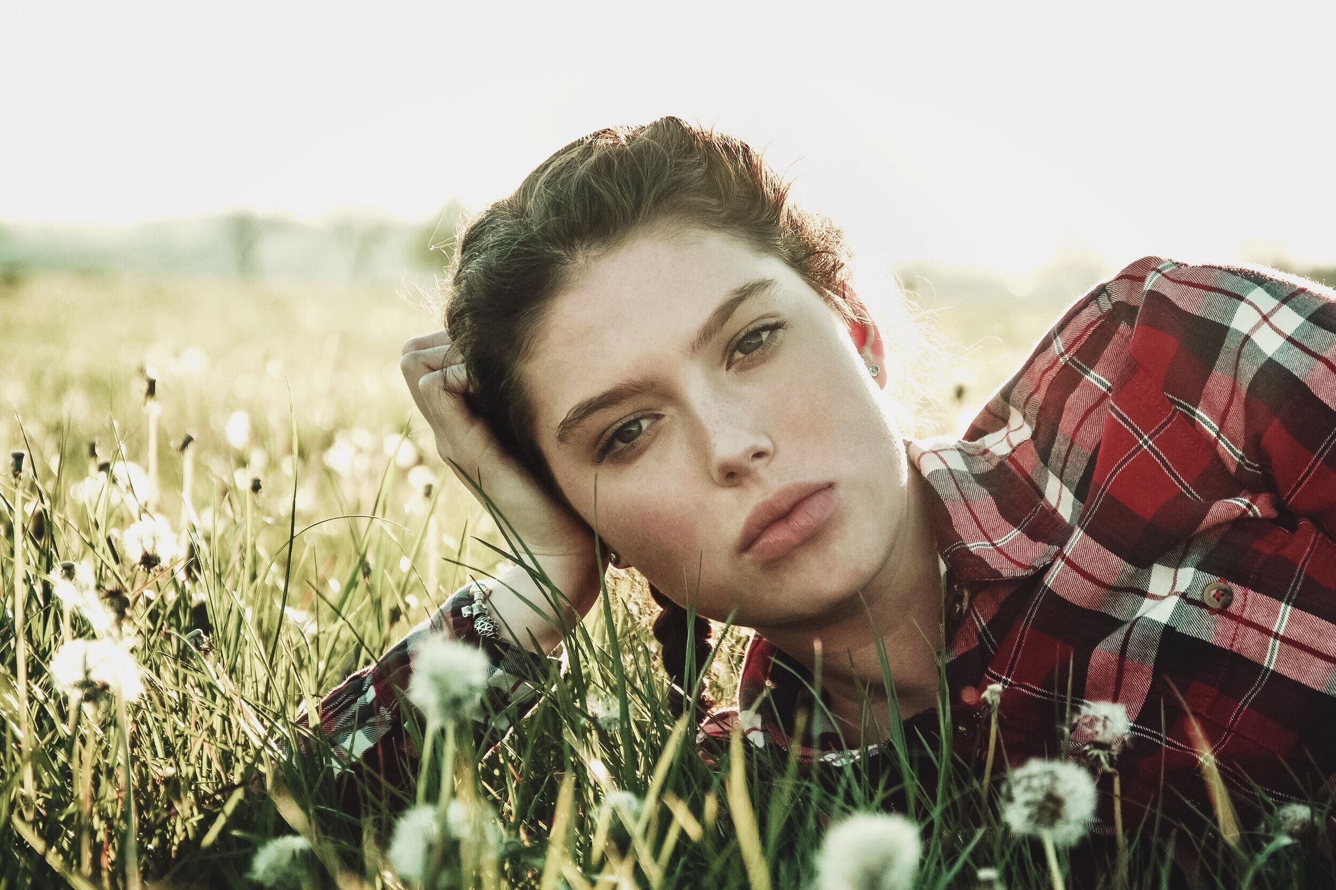 person, focus on foreground, field, lifestyles, leisure activity, flower, portrait, plant, looking at camera, young adult, close-up, growth, young women, front view, headshot, casual clothing, grass, nature