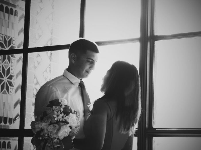 Couple kissing against window