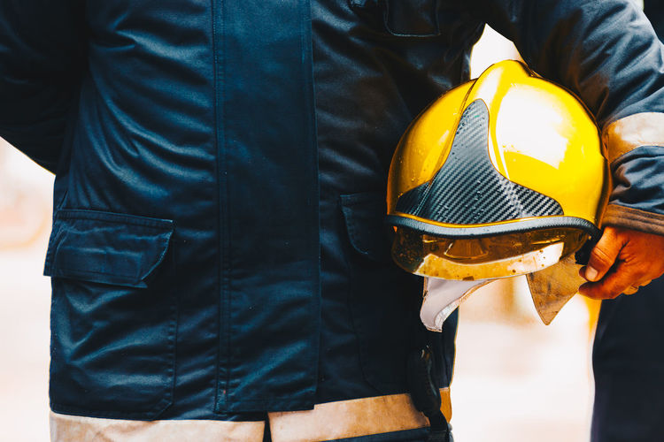 Midsection of firefighter holding helmet