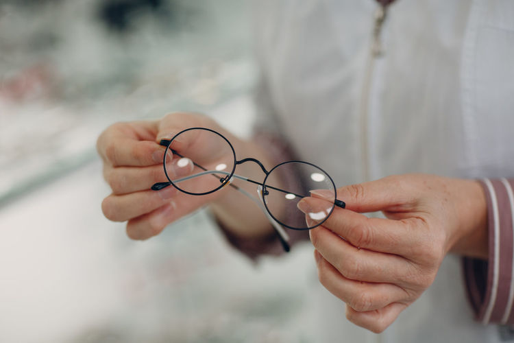 Close-up of woman hand holding eyeglasses