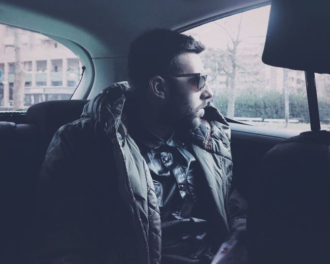 Young man looking through window while sitting in car