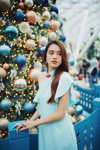 Smiling young woman looking away while standing by christmas tree outdoors