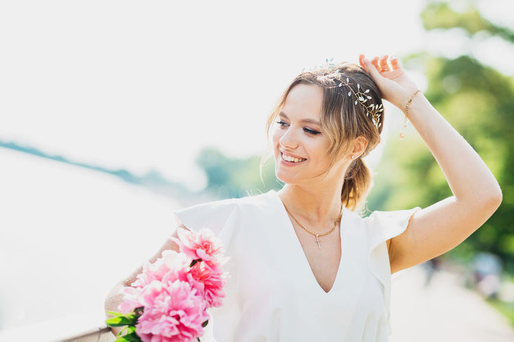 Portrait of woman with pink flowers against blurred background