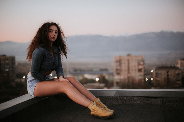 Portrait of young woman sitting outdoors during sunset