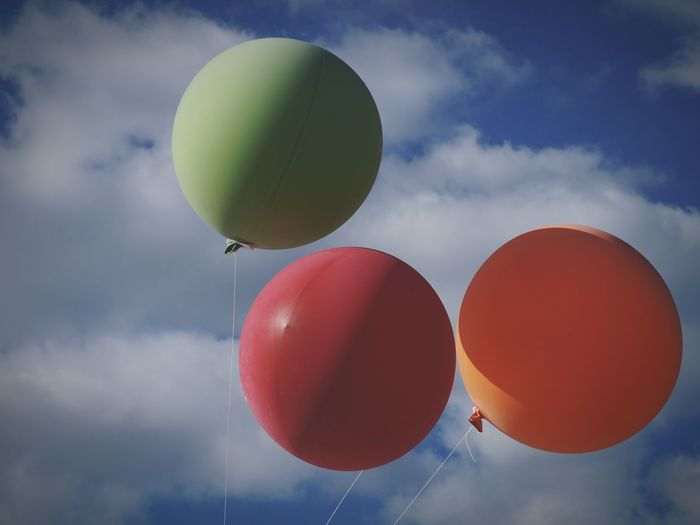 Low Angle View Of Balloons Against Cloudy Sky
