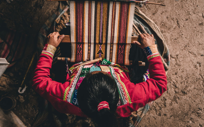 Directly above shot of woman weaving carpet