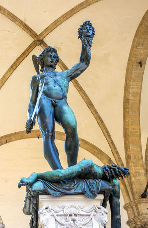 The bronze statue of Perseus hanging the head of Medusa in Florence Architecture Art And Craft Blue Bronze Building Exterior Built Structure Creativity Day Destination Florence Italy Gargoyle Human Representation Low Angle View Male Likeness Medusa No People Outdoors Perseus Sculpture Statue Statue Tourism Travel Destinations