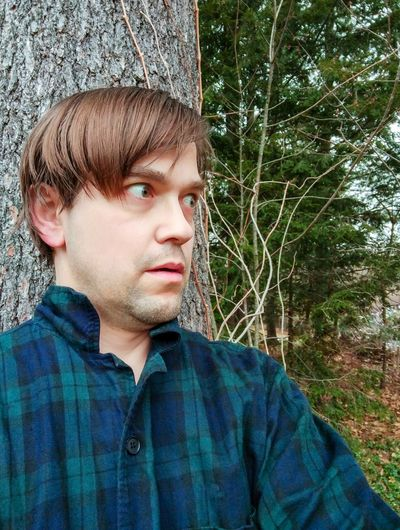 Portrait of young man looking away in forest