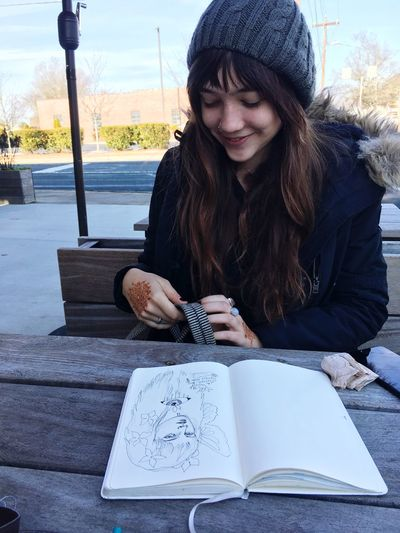 Smiling young woman sitting outdoors
