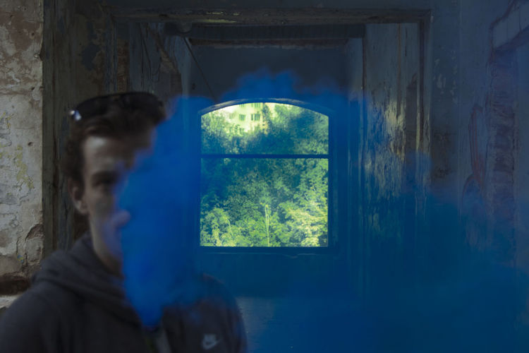 Reflection of man looking through glass window of abandoned building