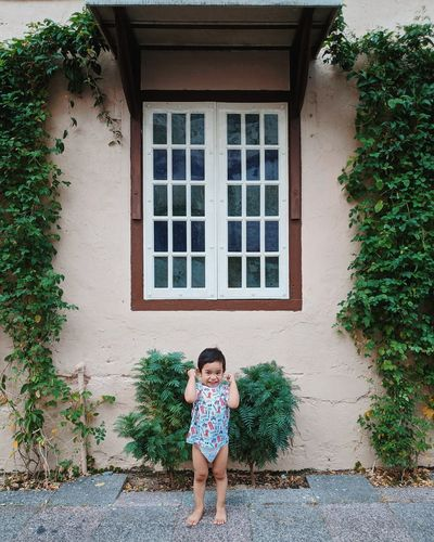 Portrait of cheerful boy standing against window amidst creeper plants