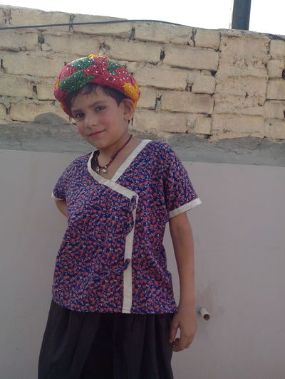 Portrait Of Girl In Traditional Clothing While Standing Against Wall