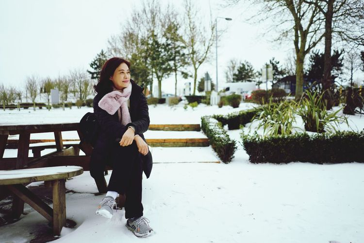 Woman Sitting On Bench At Frozen Park