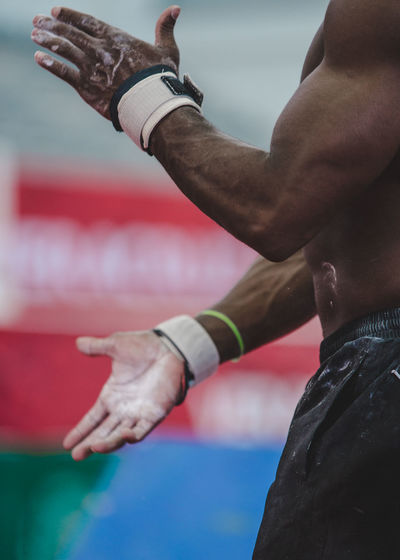 Midsection of male athlete with chalky hands
