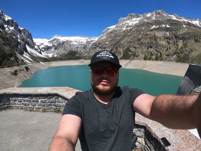 Portrait of young man in sunglasses against lake and mountains