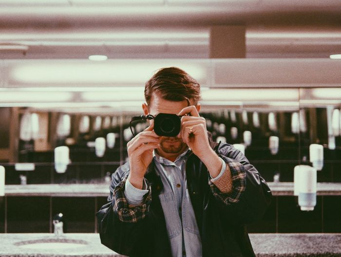 Man photographing in public restroom