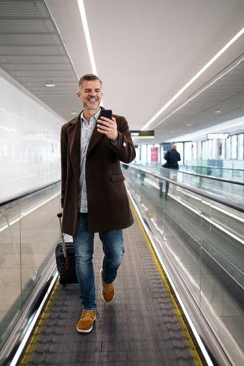 Full length portrait of man standing on railroad tracks