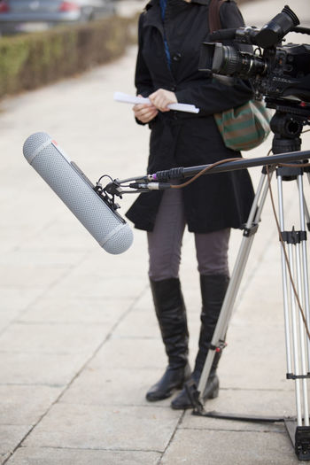 Low Section Of Journalist Standing By Television Camera On Footpath