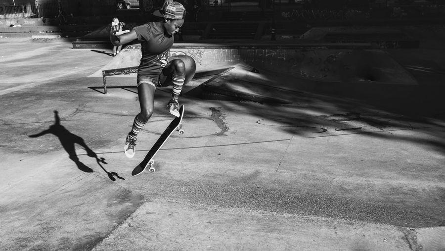 Full length of young woman skateboarding at skateboard park