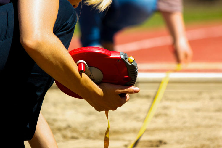 Sports event detail shot. 300mm Best Attempt Best Jump Bundesjugendspiele Cropped Depth Of Field Detail Focus On Foreground Holding Human Arm Human Body Part Human Hand Kneeling Landing Zone Long Jump Measuring Tape Pit Sand School Sports Selective Focus Sports Event  Sports Photography Winner Women