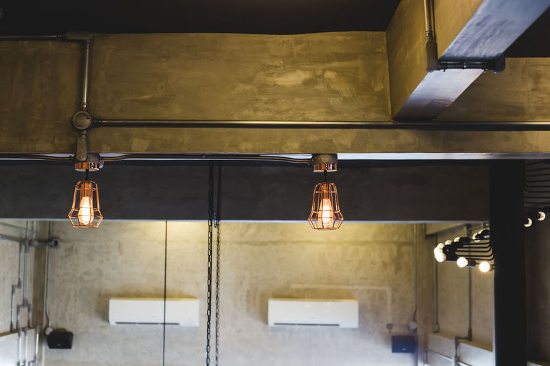 Illuminated pendant lights hanging from ceiling at home