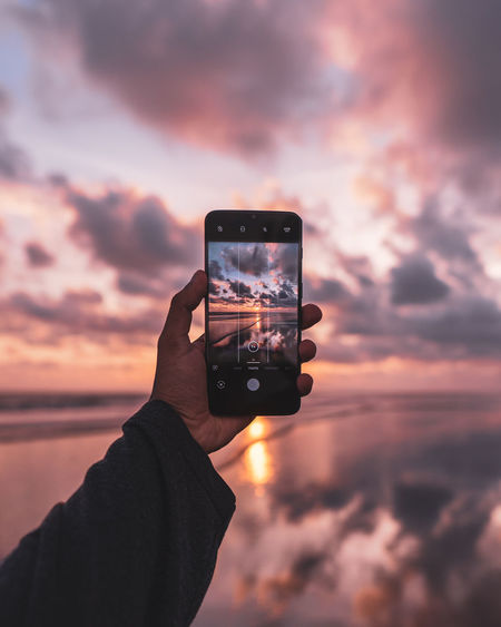 Hand holding smart phone against sky during sunset