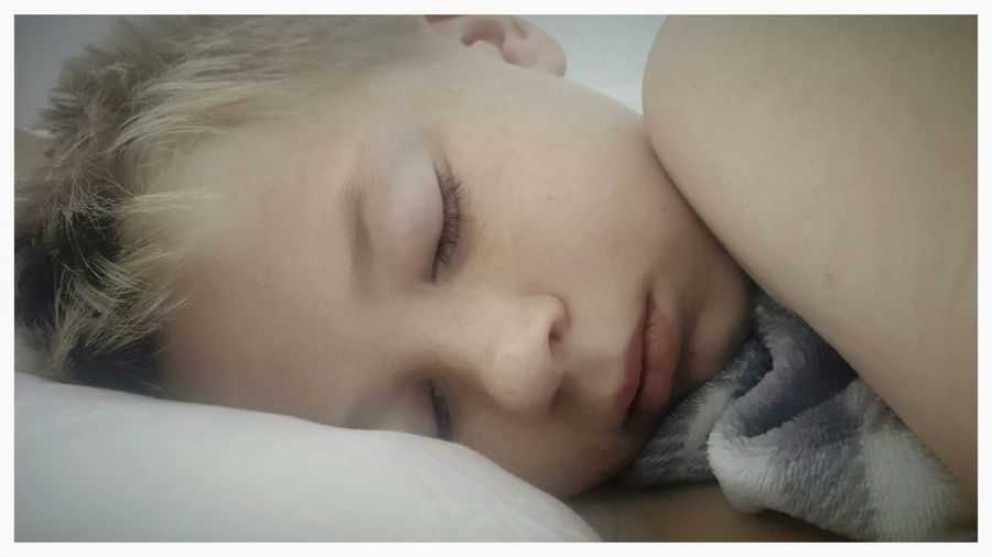 Close-up of baby sleeping on bed