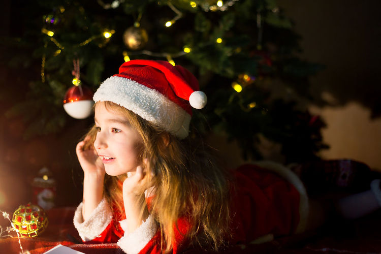 Cute girl lying down by illuminated christmas tree