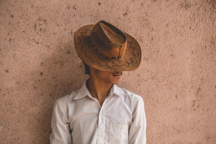 Teenage Boy Wearing Hat Standing Against Wall