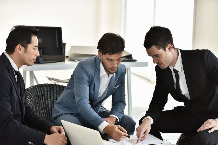 Men Businessman Office Business Business Person Meeting Cooperation Group Of People Well-dressed Communication Young Adult Young Men Indoors  Males  Adult Sitting Planning Corporate Business Discussion Teamwork Coworker Paperwork