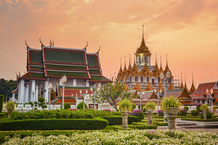 tropical swimming pool at night and Buddhist Temple in thailand Architecture Built Structure Building Exterior Building Sky Belief Religion Place Of Worship Sunset Spirituality Plant Nature Travel Destinations No People Spire  Cloud - Sky Tower Outdoors Ornate
