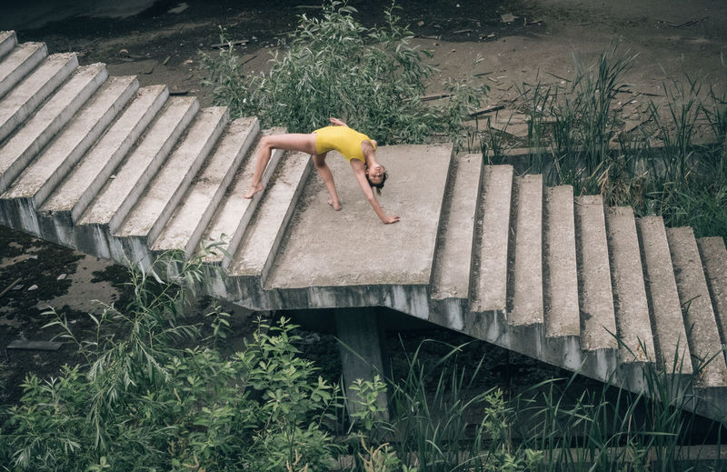 High angle view of young woman exercising on steps