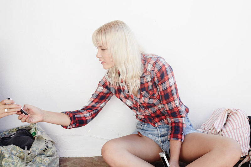 Adult Beautiful Woman Blond Hair Casual Clothing Day Holding Home Interior Indoors  Leisure Activity Lifestyles Living Room One Person People Real People Relaxation Sitting Sofa Three Quarter Length White Background Young Adult Young Women